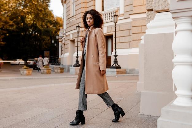 Pełnej długości modny wizerunek eleganckiej czarnej kobiety w stylowym luksusowym beżowym płaszczu i aksamitnym swetrze