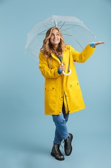 Pełnej długości obraz blondynki 20-letniej kobiety w żółtym płaszczu przeciwdeszczowym, stojącej pod przezroczystym parasolem