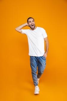 Pełnej długości obraz kaukaski facet 30s w t-shirt i dżinsy, śmiejąc się stojąc, na białym tle