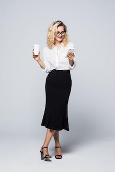 Pełnej długości obraz ładnej kobiety biznesu w wizytowym stroju i przy użyciu telefonu komórkowego z kawą na wynos w ręku na białym tle na szarej ścianie