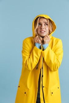 Pełnej długości obraz młodej kobiety w wieku 20 lat ubrana w żółty płaszcz przeciwdeszczowy z kapturem patrząc w górę