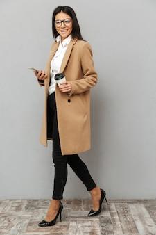 Pełnej długości obraz pięknej kobiety noszącej odzież wierzchnią na piętach, trzymając w ręku telefon komórkowy i papierowy kubek kawy na wynos, odizolowane na szarym tle