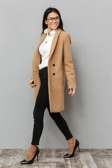 Pełnej długości obraz pięknej kobiety w okularach i beżowym płaszczu, chodzenia na piętach i patrząc z uśmiechem na bok, odizolowane na szarym tle