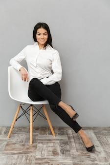 Pełnej długości obraz pięknej rzeczowej kobiety w wizytowym, siedząc na krześle w biurze, odizolowane na szarym tle
