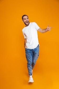 Pełnej długości obraz szczęśliwy facet 30s w koszulce i dżinsach uśmiechnięty podczas chodzenia, na białym tle