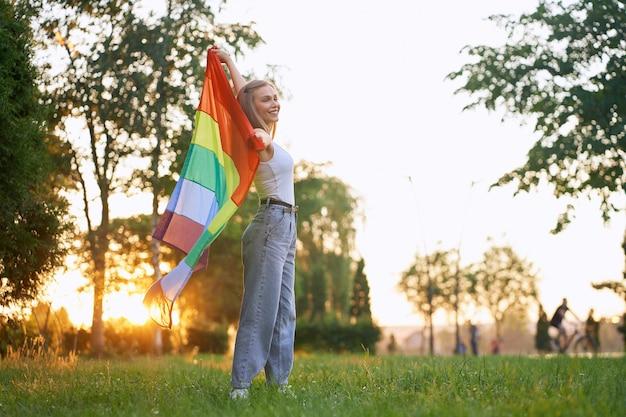 Pełnej długości od spodu widok z boku uśmiechniętej dziewczyny pozującej w parku, cieszącej się letnim zachodem słońca.