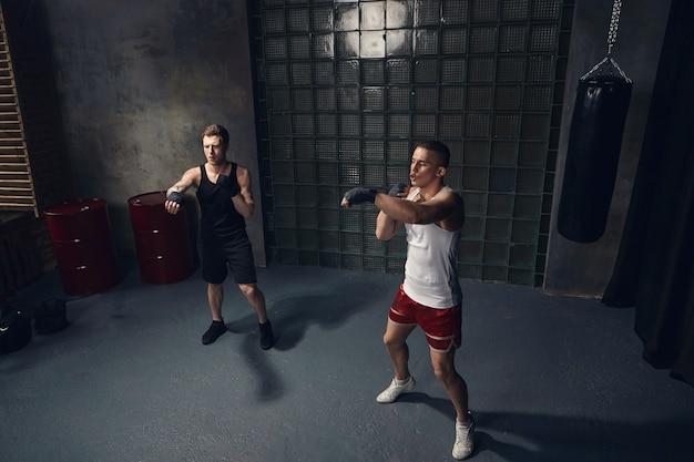 Pełnej długości odizolowany portret dwóch przystojnych facetów rasy kaukaskiej ćwiczących razem w pomieszczeniu w stylowych strojach sportowych i bandażach bokserskich, wyciągających ręce podczas opanowywania ciosów w nowoczesnej siłowni