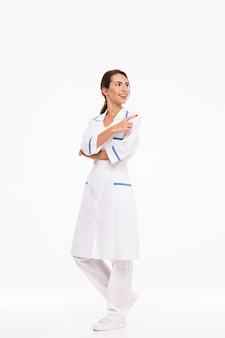 Pełnej długości pewna siebie młoda kobieta lekarz ubrany w mundur stojący na białym tle nad białą ścianą, wskazując dalej