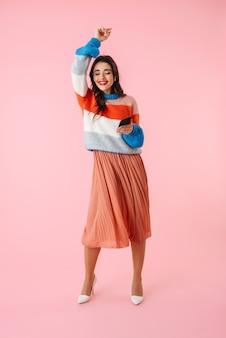 Pełnej długości piękna młoda kobieta ubrana w kolorowe ubrania, stojąca na białym tle nad różowym, słuchanie muzyki przez słuchawki, trzymając telefon komórkowy