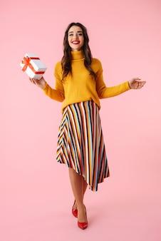 Pełnej długości piękna młoda kobieta ubrana w kolorowe ubrania, stojąca na białym tle nad różowym, trzymając pudełko