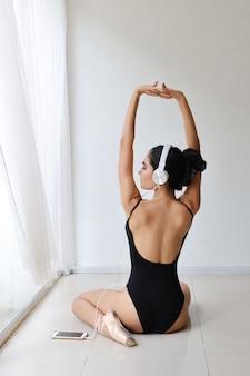 Pełnej długości piękna zdrowa i sportowa azjatykcia młoda kobieta w czarnym sportswear z hełmofonem, słucha muzykę z telefonu komórkowego podczas gdy trenujący baleta tana