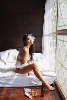 Pełnej długości pijana azjatykcia kobieta w białej bieliźnie, pije i dymi podczas gdy trzymający butelkę trunku alkohol i siedzący na łóżku w sypialni