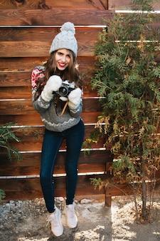 Pełnej długości pionowe ładna dziewczyna z długimi włosami w czapce i rękawiczkach, trzymając aparat na drewnianym.