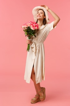 Pełnej długości pionowy portret uroczej, romantycznej kobiety w sukni i kapeluszu, trzymającej kwiaty