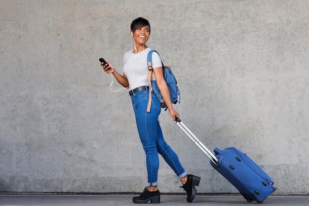 Pełnej długości podróżna młoda kobieta z telefonem komórkowym i walizką