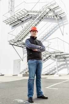 Pełnej długości portret architekta pozującego przeciwko metalowej konstrukcji