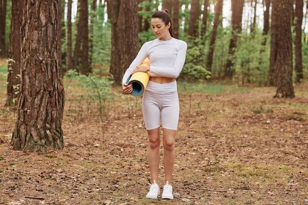 Pełnej długości portret atrakcyjna ciemnowłosa kobieta z kucykiem w białym sportowym stroju, stojąca w lesie i trzymająca w rękach karemat,