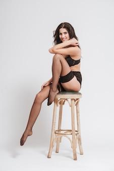 Pełnej długości portret atrakcyjnej brunetki w bieliźnie i pończochach, siedzącej na krześle i pozującej na białym tle