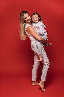 Pełnej długości portret atrakcyjnej matki rasy kaukaskiej w białej odzieży trzymającej wesołą uśmiechniętą córkę z dwoma ogonami świń w ramionach. izoluj na czerwonej ścianie.