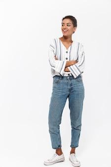 Pełnej długości portret atrakcyjnej młodej afrykańskiej kobiety stojącej na białym tle nad białą ścianą, odwracającej wzrok