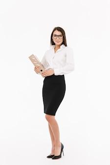 Pełnej długości portret atrakcyjnej młodej bizneswoman noszącej formalne ubrania, stojącej na białym tle nad białą ścianą, trzymającej folder