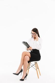 Pełnej długości portret atrakcyjnej młodej bizneswoman w wizytowym stroju, siedzącej na krześle na białym tle nad białą ścianą, przy użyciu telefonu komórkowego, trzymając folder