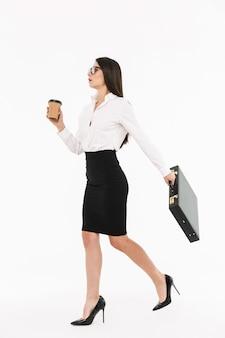Pełnej długości portret atrakcyjnej młodej bizneswoman w wizytowym stroju spacerującej na białym tle nad białą ścianą, niosącej teczkę, pijącej kawę na wynos