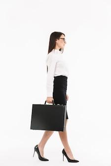 Pełnej długości portret atrakcyjnej młodej bizneswoman w wizytowym stroju spacerującej na białym tle nad białą ścianą, niosącej teczkę
