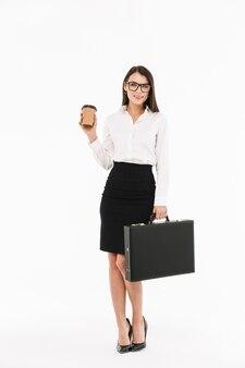 Pełnej długości portret atrakcyjnej młodej bizneswoman w wizytowym stroju stojącej na białym tle nad białą ścianą, niosącej teczkę, pijącej kawę na wynos