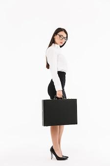 Pełnej długości portret atrakcyjnej młodej bizneswoman w wizytowym stroju stojącej na białym tle nad białą ścianą, niosącej teczkę