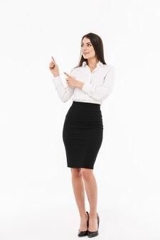 Pełnej długości portret atrakcyjnej młodej bizneswoman w wizytowym stroju stojącej na białym tle nad białą ścianą, przedstawiającej miejsce na kopię