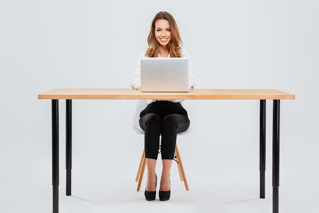 Pełnej długości portret atrakcyjnej uśmiechniętej bizneswoman za pomocą laptopa siedząc przy biurku na białym tle
