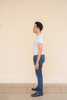 Pełnej długości portret azjatyckiego mężczyzny noszącego białą koszulkę na prostym tle na zewnątrz