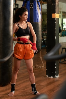 Pełnej długości portret boksera muay thai owijającego czerwony pasek na nadgarstku przed treningiem