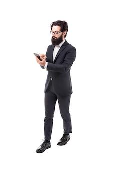Pełnej długości portret brodaty biznesmen ze smartfonem, na białym tle