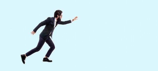 Pełnej długości portret brodaty, modny biznesmen biegnący przed niebieską ścianą, mężczyzna wyciąga rękę do przodu, aby coś złapać, obraz panoramiczny