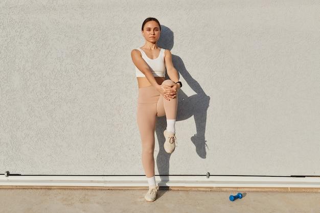 Pełnej długości portret ciemnowłosej kobiety na sobie biały sportowy top i beżowe legginsy patrząc na kamery z poważnym wyrazem twarzy, stojąc, rozciągając nogę przed treningiem, zdrowy styl życia.