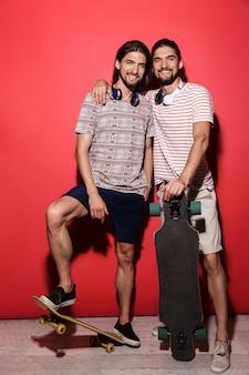 Pełnej długości portret dwóch młodych uśmiechniętych braci bliźniaków