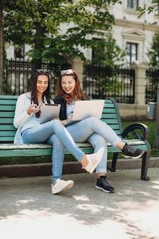 Pełnej długości portret dwóch pięknych kobiet siedzących na ławce na zewnątrz, patrząc na tablet i laptopa, śmiejąc się i pijąc kawę.