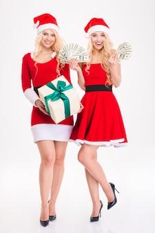 Pełnej długości portret dwóch uśmiechniętych bliźniaczek uwodzicielskich blond sióstr w czerwonych sukienkach i czapkach świętego mikołaja z pieniędzmi i prezentem na białym tle