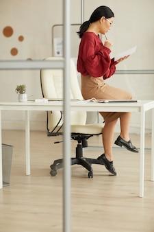 Pełnej długości portret eleganckiej bizneswoman azjatyckiego siedzi na biurku w nowoczesnym biurze biały, kopia przestrzeń