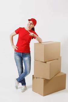Pełnej długości portret kobiety dostawy w czerwonej czapce, t-shirt na białym tle. kobieta kurier lub dealer stojący w pobliżu pustych kartonów. odbieranie pakietu. skopiuj miejsce na reklamę.