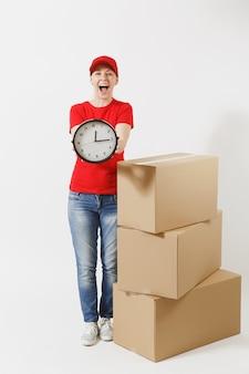 Pełnej długości portret kobiety dostawy w czerwonej czapce, t-shirt na białym tle. kobieta kurier w pobliżu pustych kartonów, trzymając okrągły zegar, pokazując w czasie. odbieranie pakietu. skopiuj miejsce.