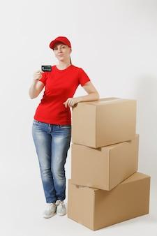Pełnej długości portret kobiety dostawy w czerwonej czapce, t-shirt na białym tle. kobieta kurier w pobliżu pustych kartonów z kartą kredytową. odbieranie pakietu. skopiuj miejsce na reklamę.