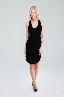 Pełnej długości portret kobiety szczęśliwy moda pozowanie w czarnej sukni na białym tle na białym tle