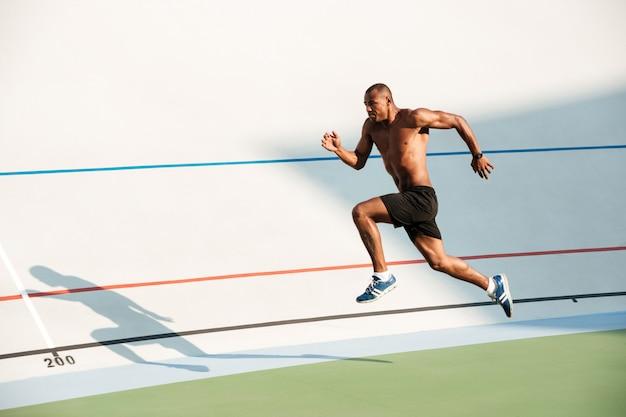 Pełnej długości portret lekkoatletycznego półnagi sportowca skoki