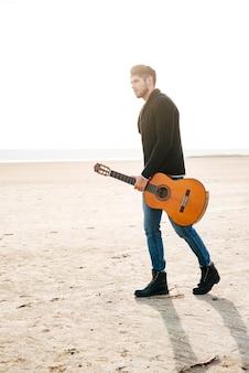 Pełnej długości portret męskiego muzyka spacerującego po plaży z gitarą