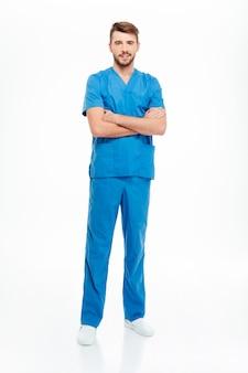 Pełnej długości portret mężczyzny lekarza stojącego z założonymi rękoma na białym tle na białym tle