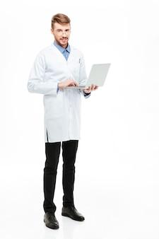 Pełnej długości portret mężczyzny lekarza trzymającego laptopa i patrzącego na kamerę na białym tle