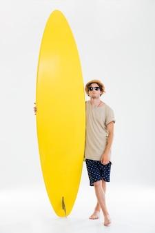 Pełnej długości portret mężczyzny na plaży w okularach przeciwsłonecznych i kapeluszu, trzymając deskę surfingową na białym tle na białej ścianie